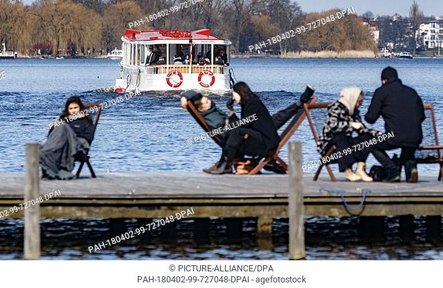 02 April 2018, Germany, Hamburg: Inhabitants of Hamburg enjoy the sunny Easter Monday weather on deckchairs at the Outer Alster