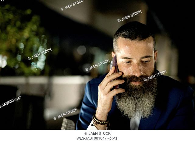 Portrait of bearded man telephoning on a terrace