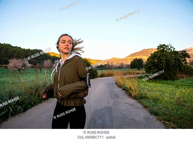 Young woman running along rural road, wearing activity tracker