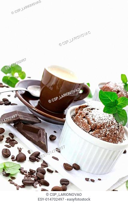 Chocolate muffin with cup of coffee and scattered grain of coffee