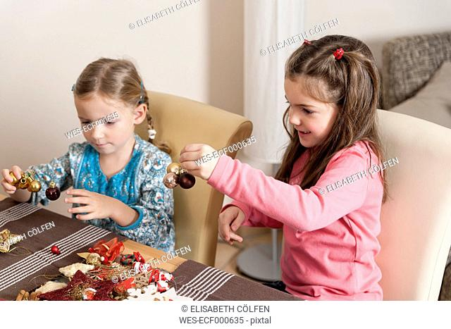 Two little girls tinkering Christmas decoration