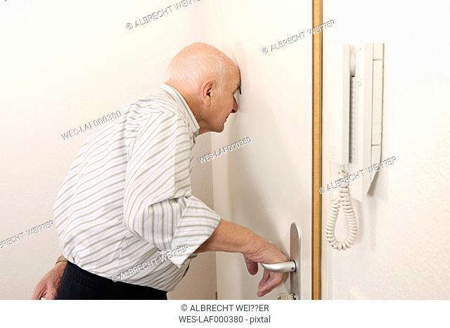 Old man looking through peephole of apartment door