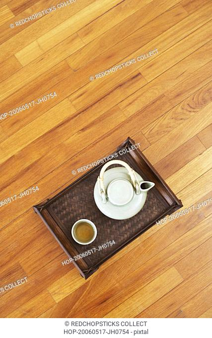 High angle view of a teapot and a tea cup with a tray on a hardwood floor