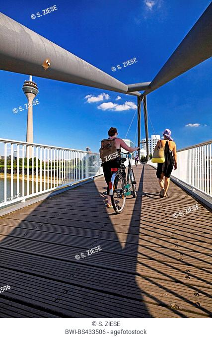 people on the harbor bridge with Rhein tower and Neuer Zollhof, Germany, North Rhine-Westphalia, Duesseldorf