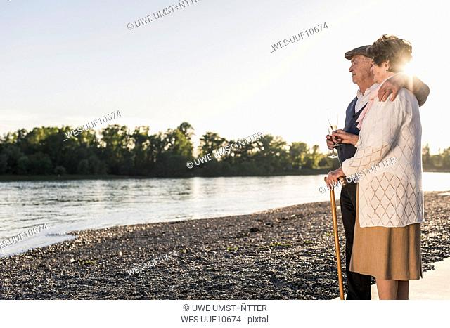 Senior couple on the beach with Champagne glasses at sunset