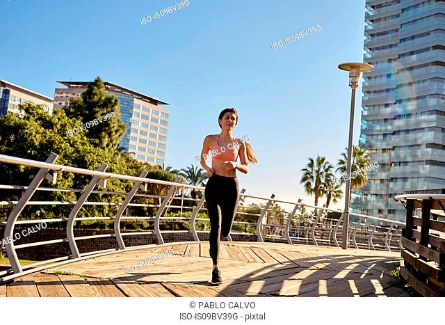 Woman jogging in city park, Barcelona, Catalonia, Spain