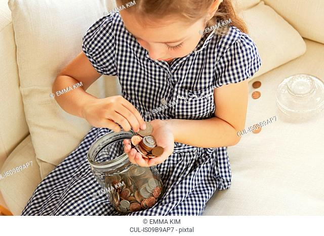Young girl, sitting on sofa, counting money from jar, elevated view