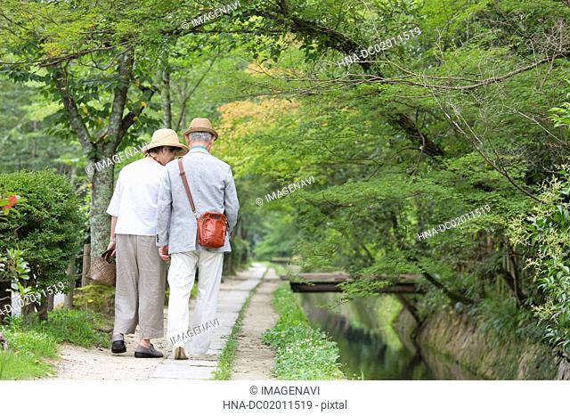 Senior couple walking along riverside footpath