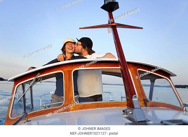 Man kissing woman on motorboat
