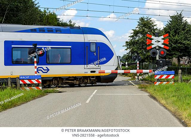 HOEVEN, THE NETHERLANDS - AUGUST 1: Train moving at high speed on a level crossing on August 1, 2016 in The Netherlands
