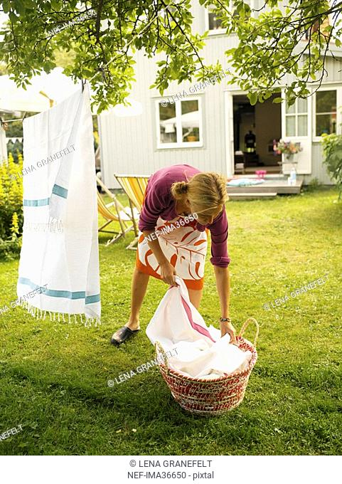 Woman hanging laundry in a garden