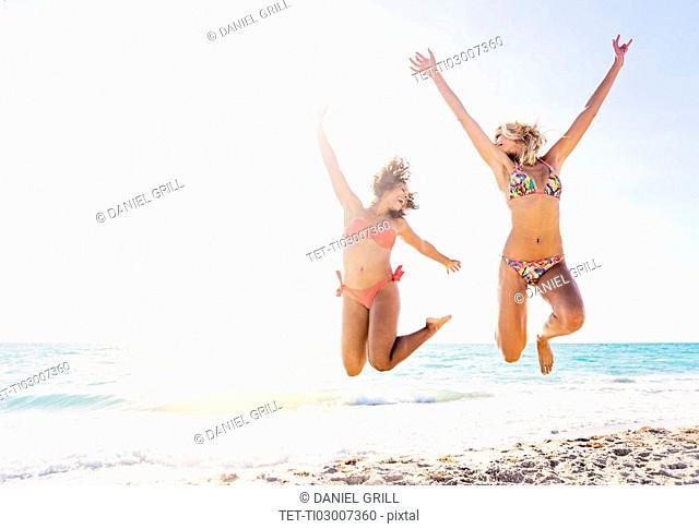 Female friends jumping on beach
