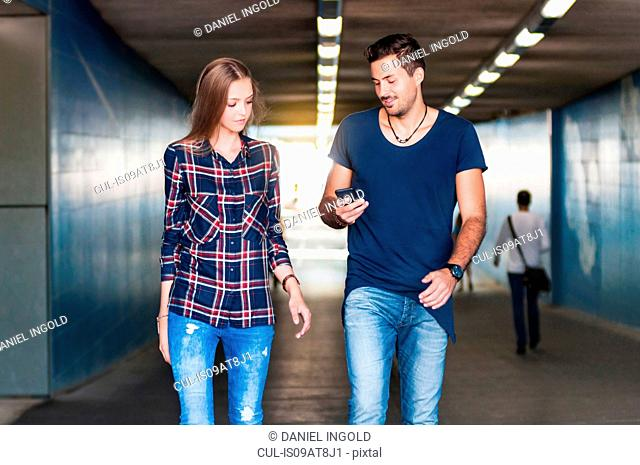 Young couple strolling and reading text message in underpass
