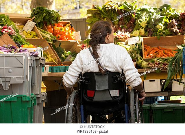 Woman with spinal cord injury in wheelchair shopping at outdoor market