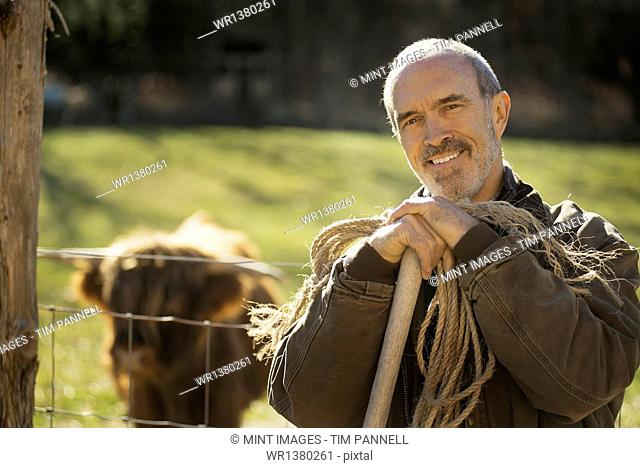 A man with a wooden staff and a coil of rope beside an animal pen. A highland cow with horns. Working on an organic farm