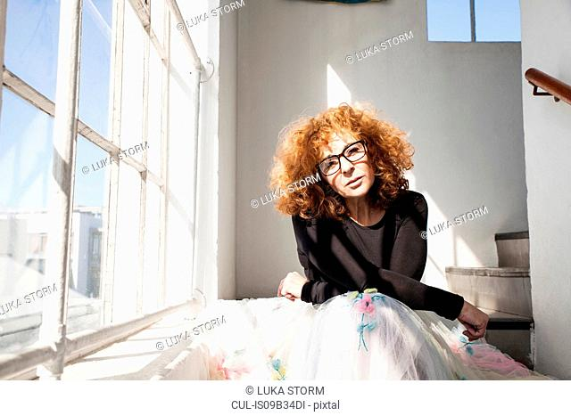 Woman sitting on stairway looking at camera