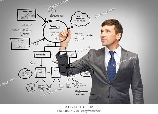 business, new technology and office concept - attractive buisnessman or teacher with marker drawing plan