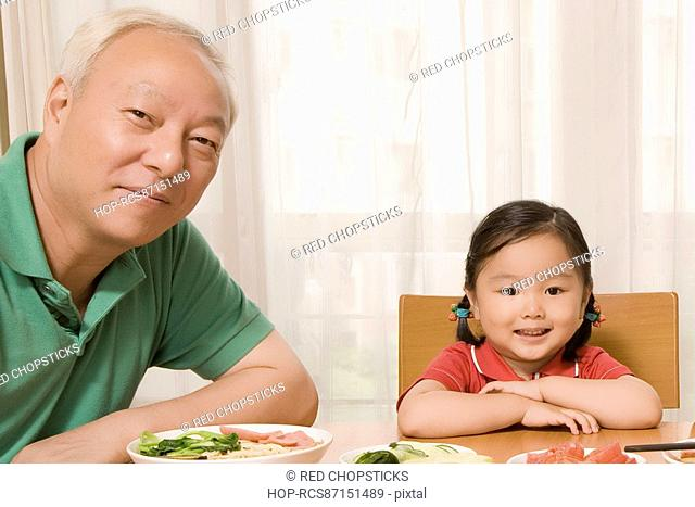 Portrait of a mature man sitting with his granddaughter at a dining table