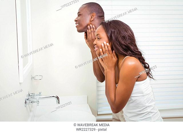 Ethnic couple looking in the mirror