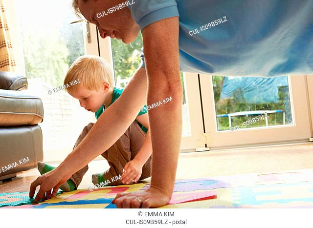 Boy and father playing with floor jigsaw puzzle