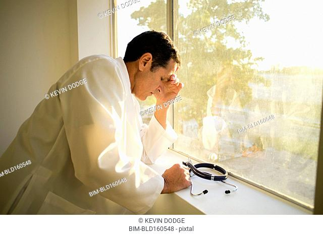 Stressed Hispanic doctor standing at window