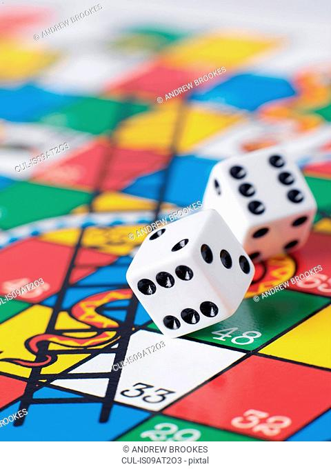 Dice falling onto snakes and ladders board