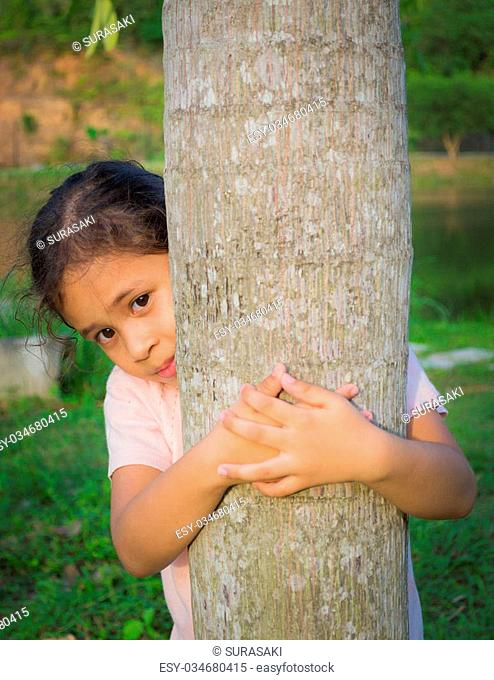 A cute girl is behind a tree under sunlight