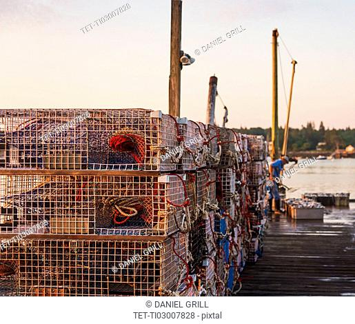 Stacks of lobster traps on jetty at sunrise with man working in background