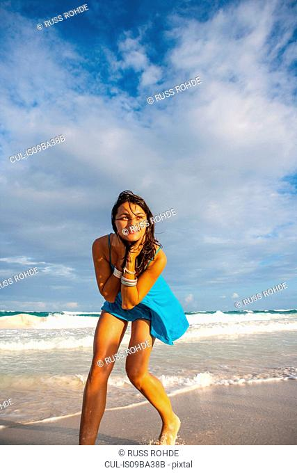 Young woman in sundress playing on beach, Tulum, Quintana Roo, Mexico
