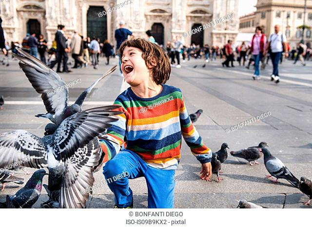 Boy laughing while feeding pigeons in square, Milan, Lombardy, Italy