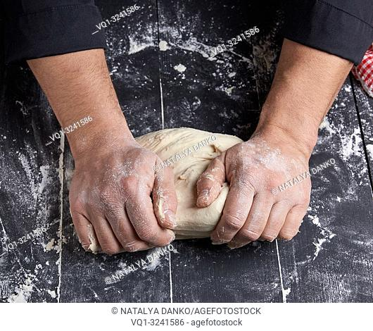 baker kneads white wheat flour dough on a black wooden table, top view