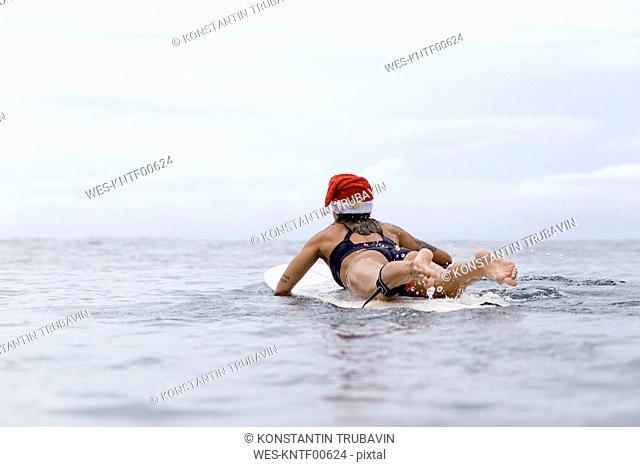 Indonesia, Bali, woman on surfboard wearing Santa hat