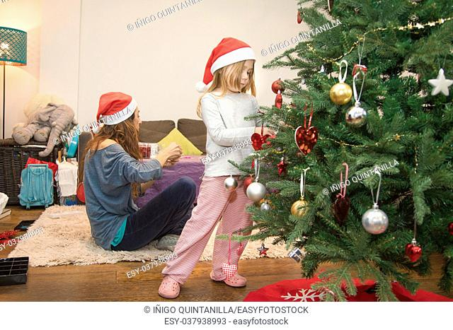 four years blonde cute child with red Santa Claus hat decorating a Christmas tree, with mother helping behind, at home