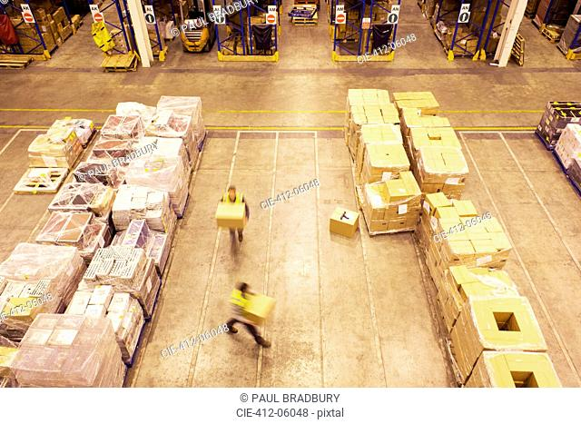 Blurred view of workers carrying boxes in warehouse