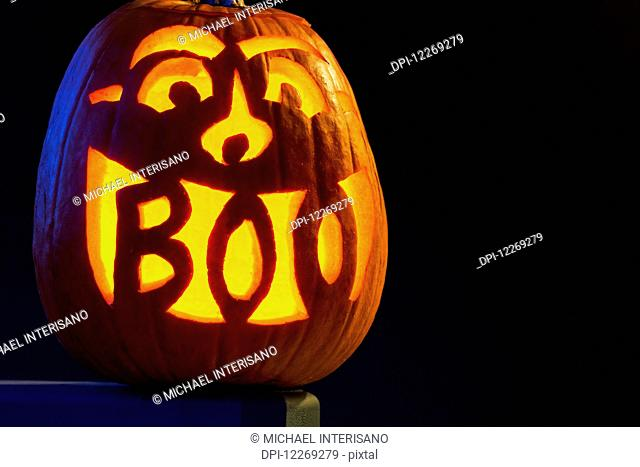 Carved pumpkin glowing with the word Boo carved in mouth; Calgary, Alberta, Canada