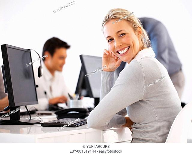 Smiling customer care representative sitting in front of computer with colleagues in background