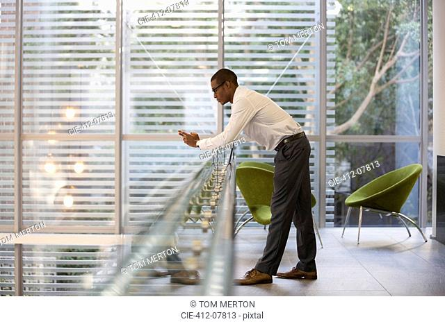 Businessman leaning on railing in office and text messaging with cell phone