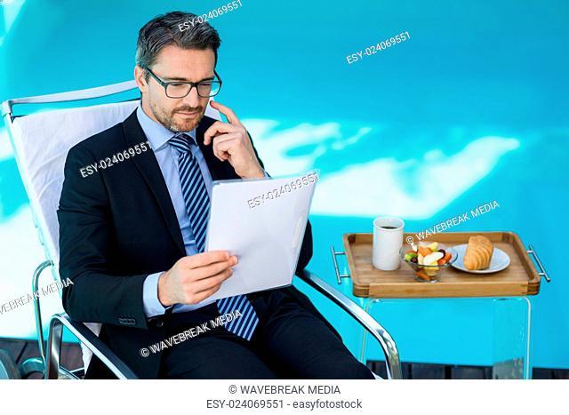 Smart man reading document near pool