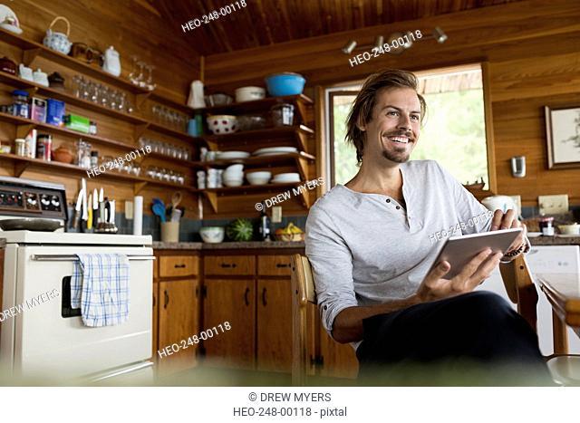 Smiling man using digital tablet cabin kitchen table