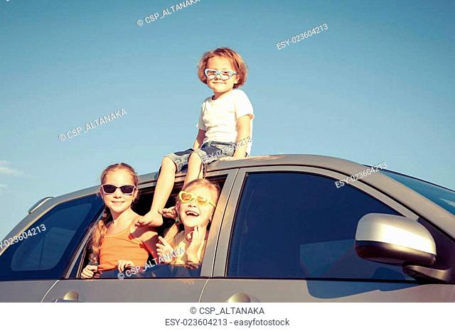 Happy brother and his two sisters are sitting in the car