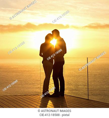 Silhouette of couple at sunset over ocean