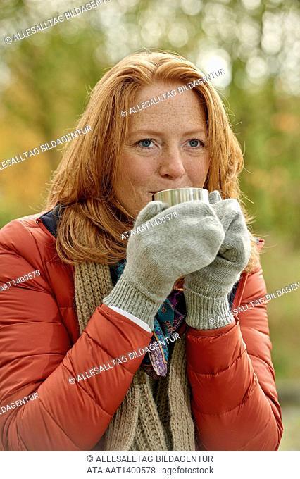 Freezing woman is drinking hot tea