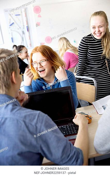Teenage girls laughing in classroom