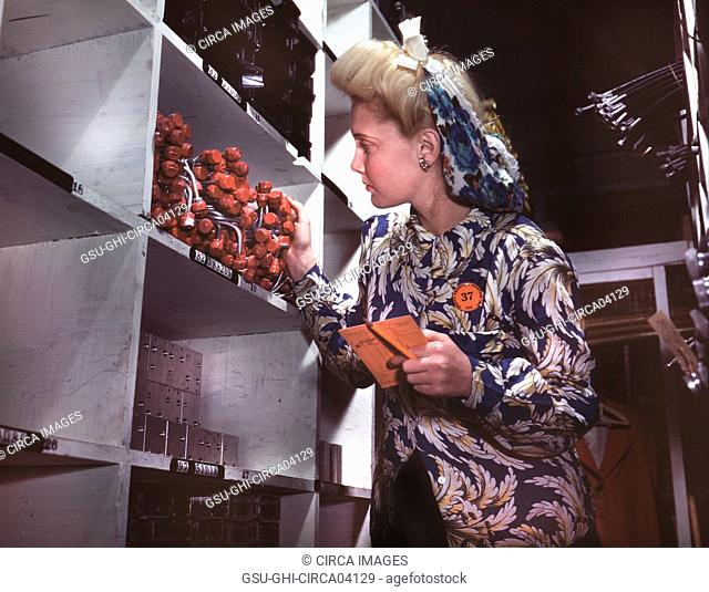Female Clerk Checking to see if proper Numbers of Parts were Received and Placed in Proper Bins in Stock Room, North American Aviation, Inc