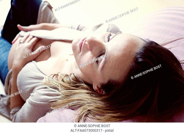 Pregnant woman relaxing with eyes closed, high angle view
