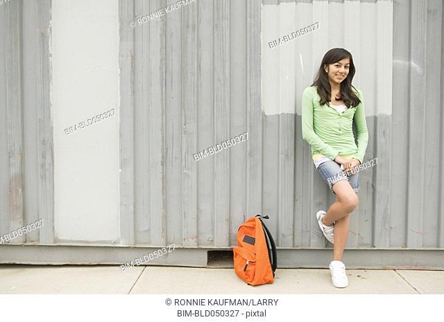 Hispanic teenaged girl leaning on wall