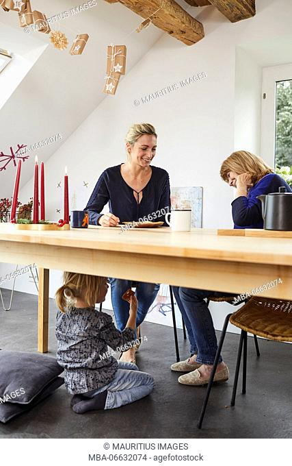 Grandmother, mother and little daughter with advent wreath, sitting at kitchen table
