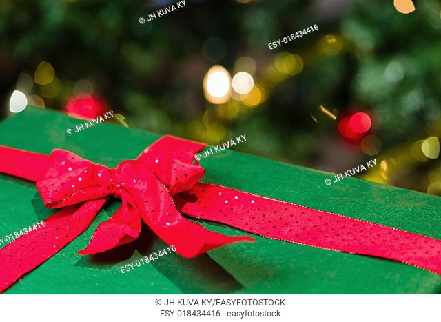 Christmas gift with a bow, Christmas tree on background