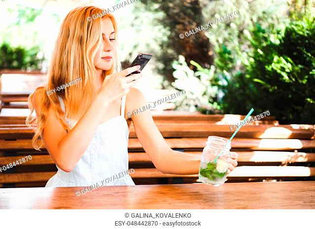 Blond girl sitting at a wooden table in a summer cafe with a cocktail and taking picture of food with mobile phone