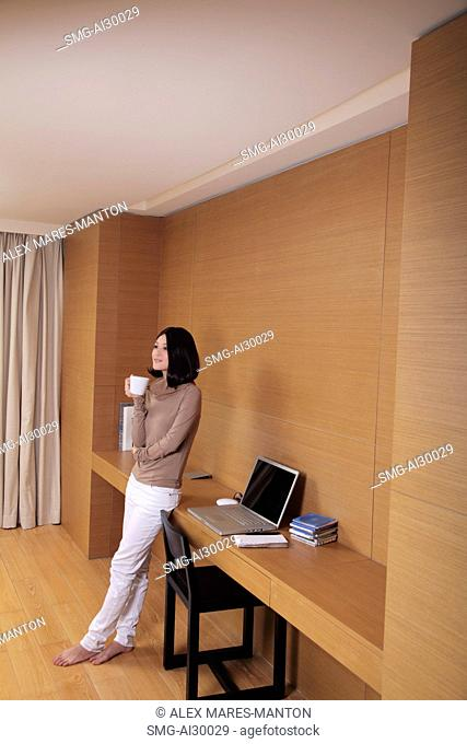 Young woman leaning next to desk holding coffee